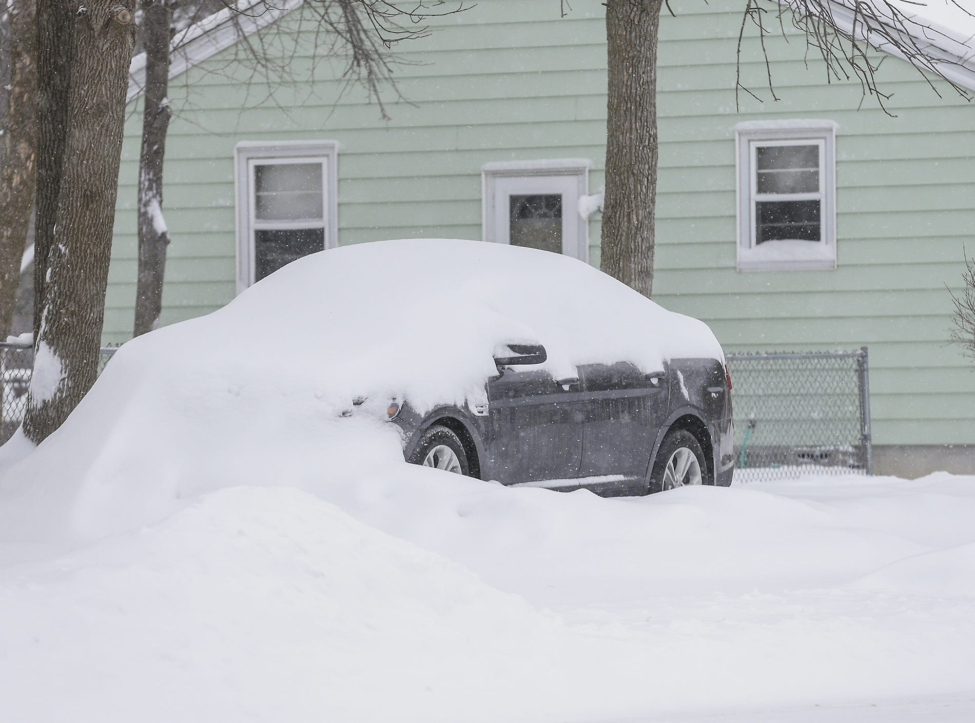 A car is partialy burried in snow Monday, Jan. 28, 2019, in Fond du Lac during a snow storm that hampered travel and closed businesses and schools in the Fond du Lac area. This was the Fond du Lac area's second snow storm in five days.