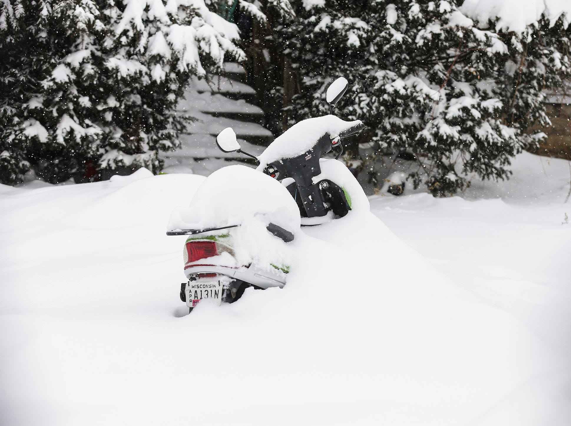 A motor bike sits burried in snow Monday, Jan. 28, 2019, in Fond du Lac, Wisconsin during a snow storm that hampered travel and closed businesses and schools in the Fond du Lac area. This was the Fond du Lac area's second snow storm in five days.