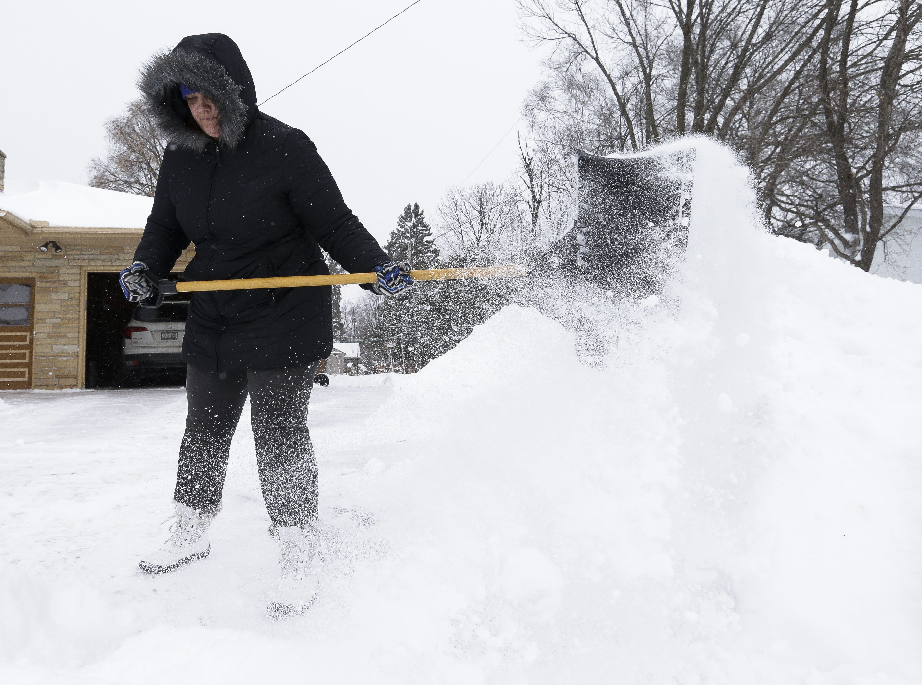 Jennifer Nickel shovels out her driveway on Monday, Jan. 28, 2019, in Stevens Point, Wis. A winter storm rolled through Wisconsin on Sunday and Monday, marking the first major snowfall of the season.