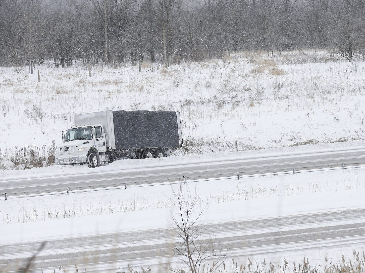 A Fond du Lac County Sheriff's officer tends to a box truck in the ditch Monday, Jan. 28, 2019, on I-41 near Main Street during a snow storm that hampered travel and closed businesses and schools in the Fond du Lac, Wisconsin area. This was the Fond du Lac areas second snow storm in five days.