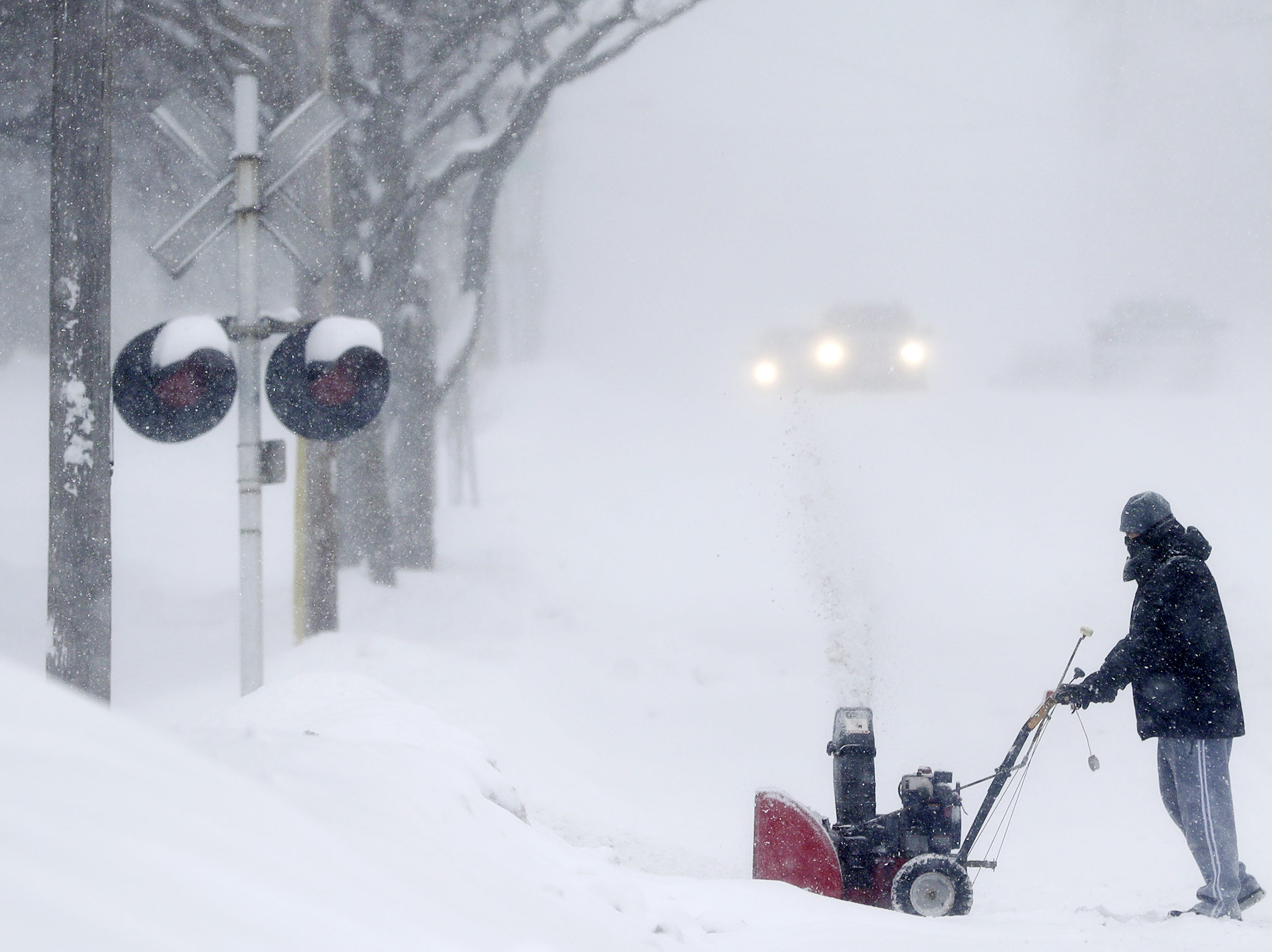 A resident uses a snowblower on his driveway during a snowstorm on Monday, Jan. 28, 2019, in Green Bay, Wis.