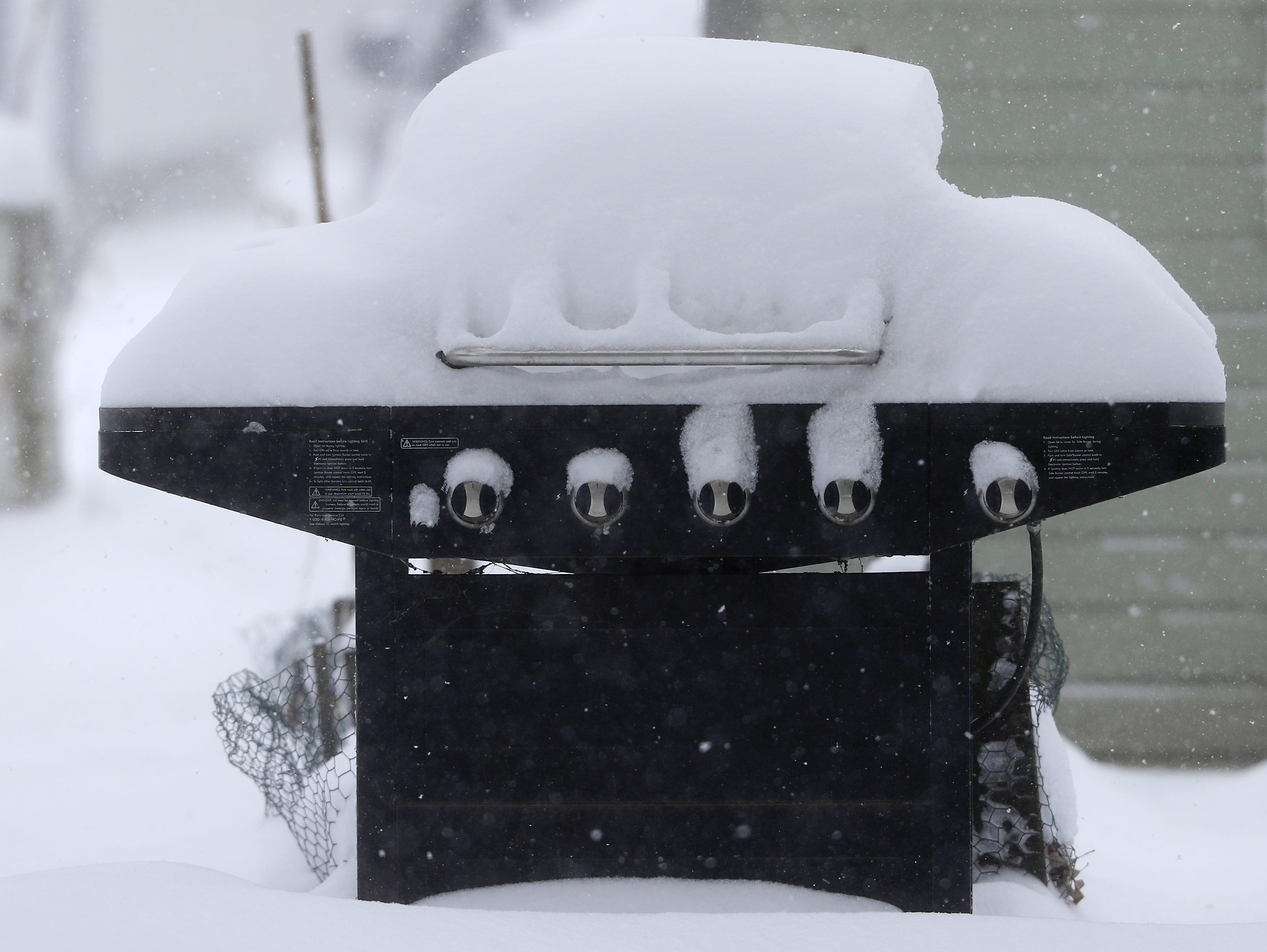A grill is covered in snow during a snowstorm on Monday, Jan. 28, 2019, in Green Bay, Wis.