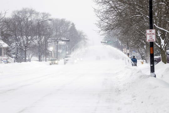 A person is seen snowblowing a sidewalk Monday, Jan. 28, 2019, on Johnson Street in Fond du Lac, Wisconsin during a snow storm that hampered travel and closed businesses and schools in the Fond du Lac area. This was the Fond du Lac areas second snow storm in five days.
