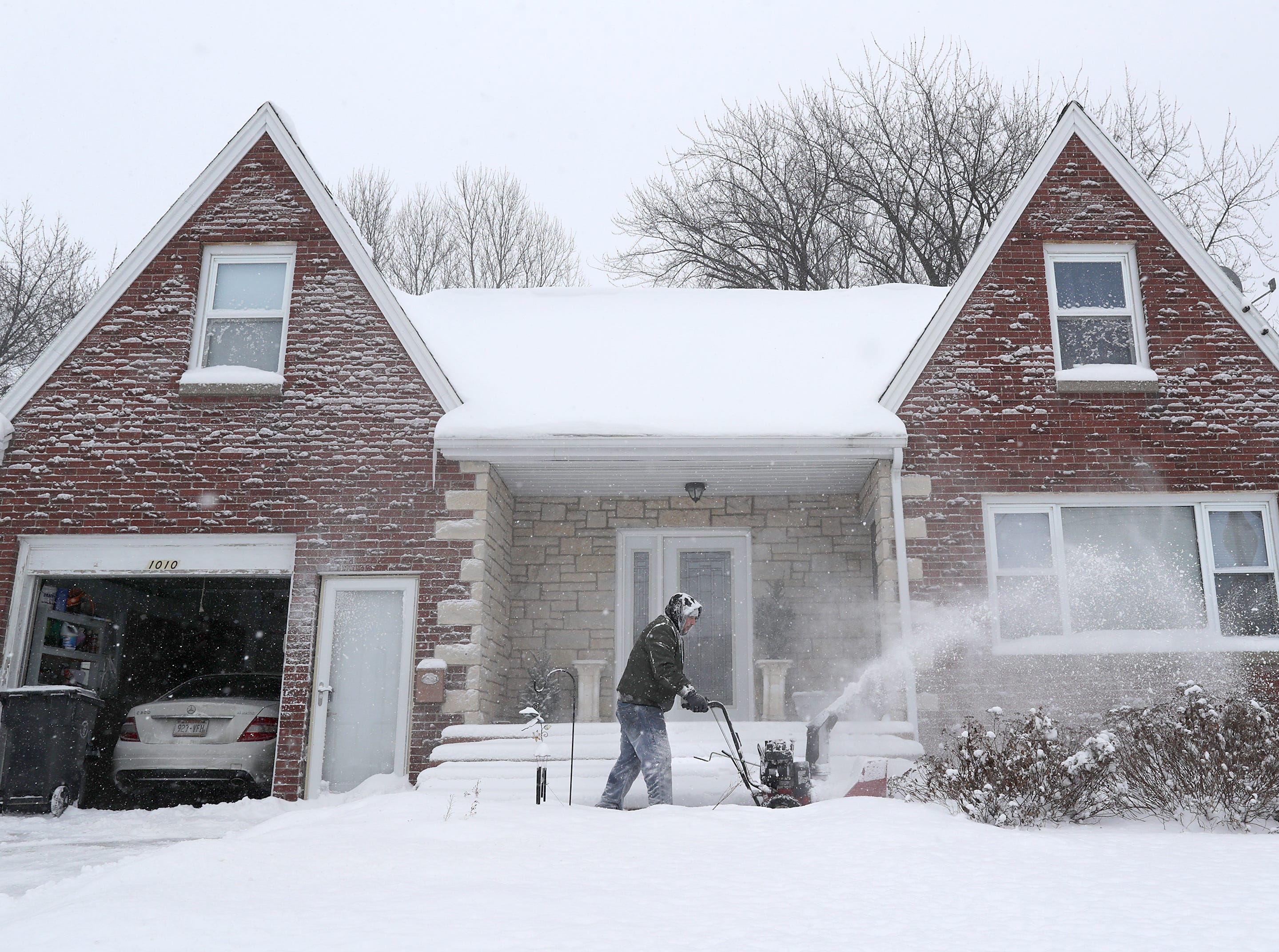 Jim Justin a clears a sidewalk as a winter storm moves through Wisconsin on Monday, Jan. 28, 2019, in Little Chute, Wis.