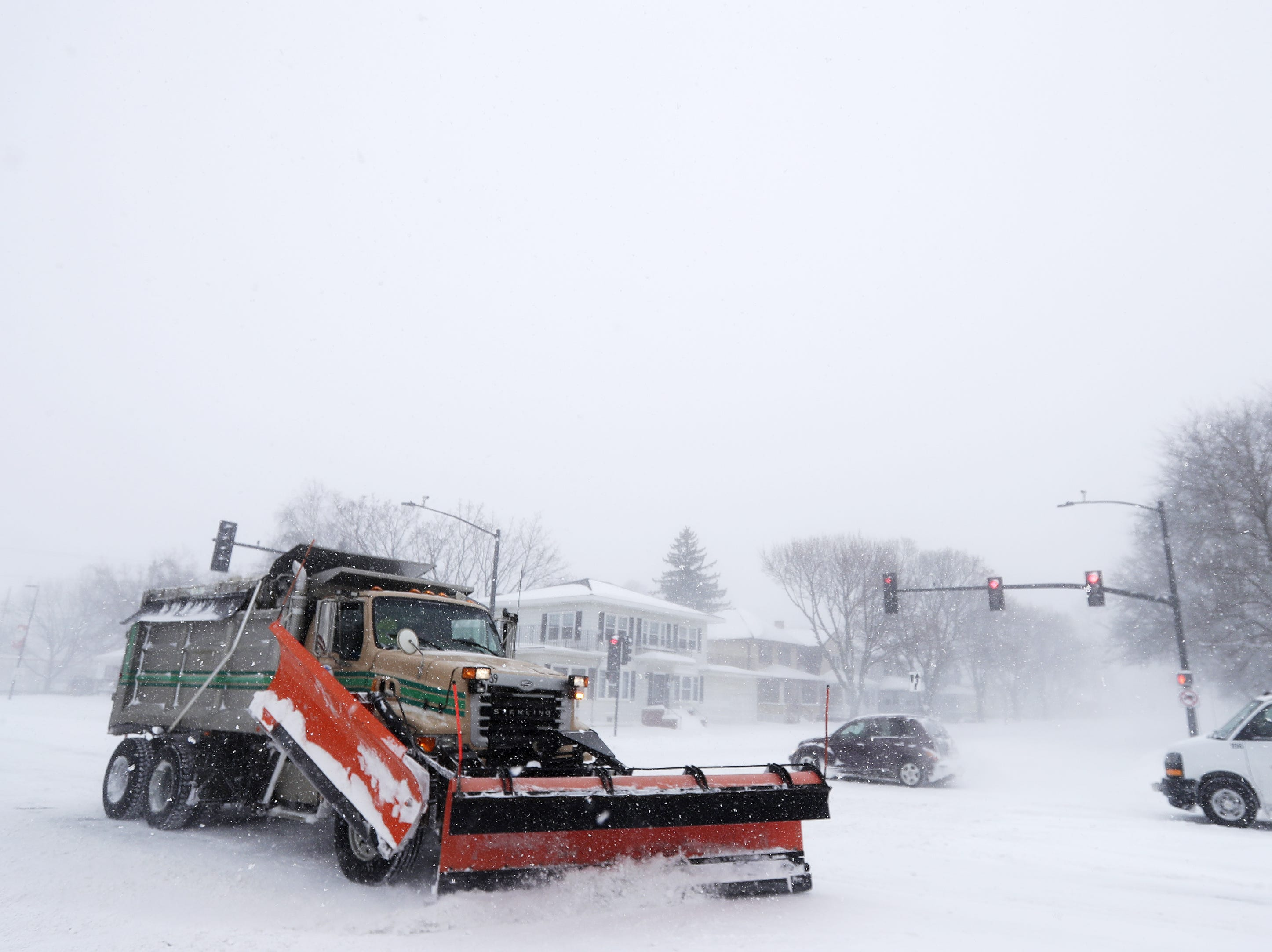 City snow plows clear streets during a snowstorm on Monday, Jan. 28, 2019, in Green Bay, Wis.