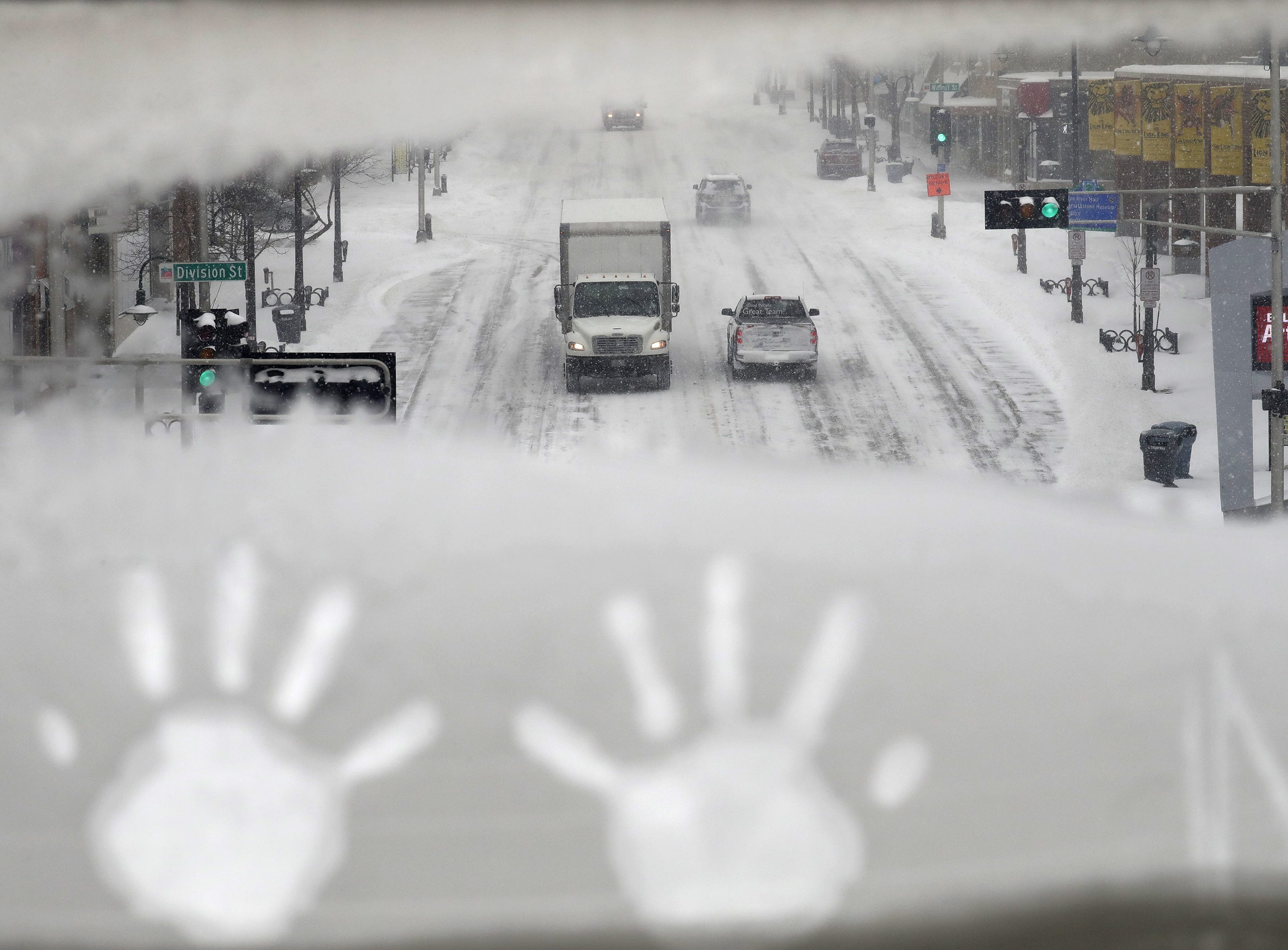 Hand prints are left behind as traffic moves slowly along College Avenue during a snowstorm Monday, Jan. 28, 2019, in downtown Appleton, Wis.
