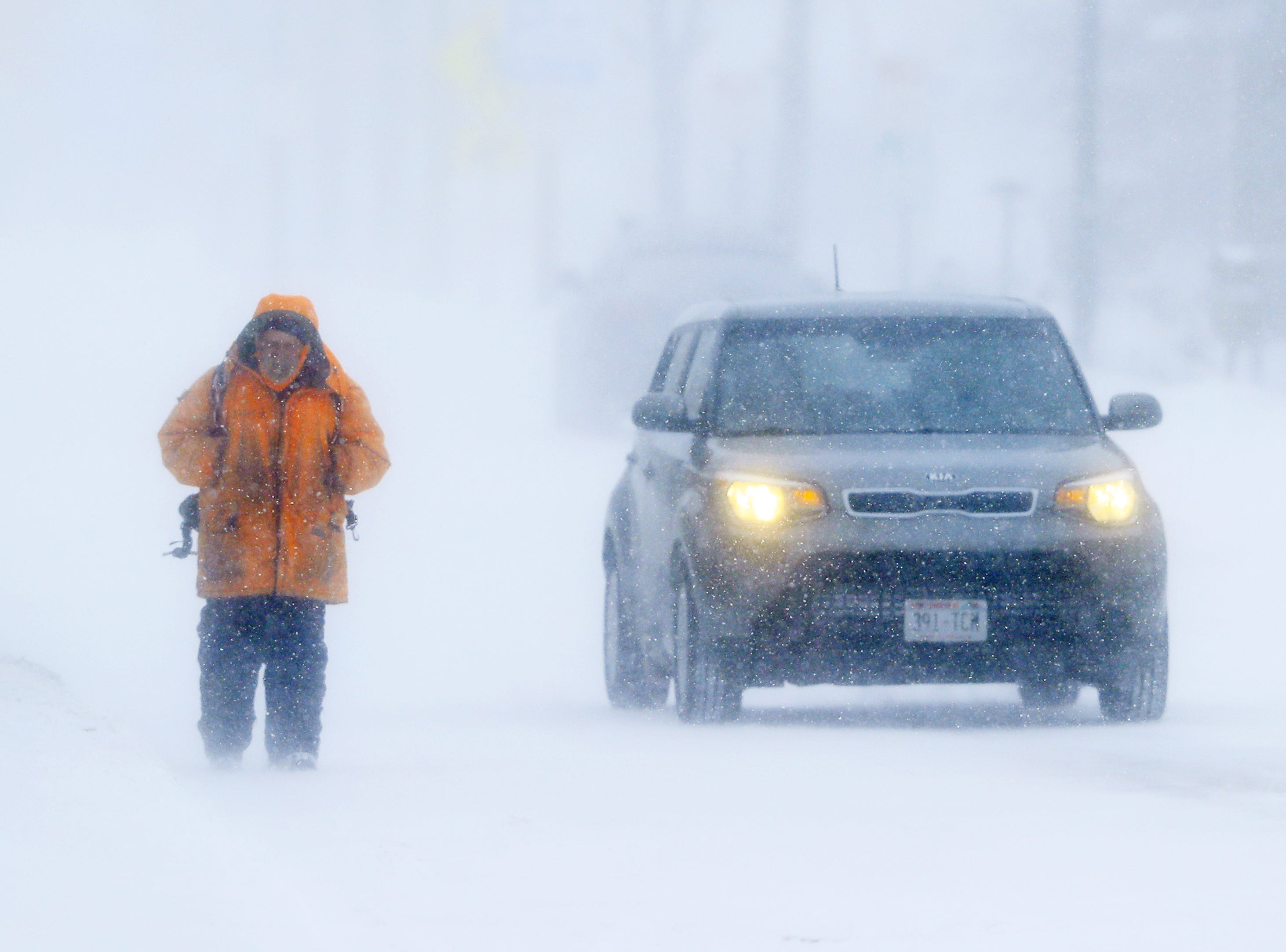 A man walks along Broadway during a snowstorm on Monday, January 28, 2019 in Green Bay, Wis.