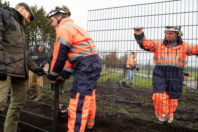 Workers erect a fence along the Denmark Germany border at Padborg, Denmark, Monday Jan. 28, 2019. Denmark has begun erecting a 43.4-mile fence along the German border to keep out wild boars in an attempt to prevent the spread of African swine fever, which could jeopardize the country's valuable pork industry.