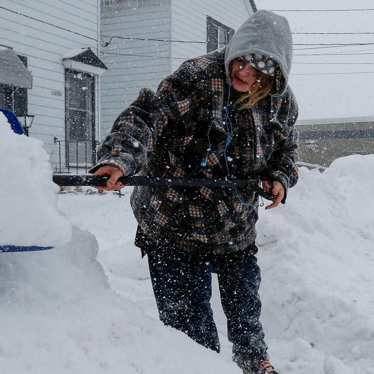 Crystal Oestreich, of Manitowoc, Wisc., shovels her neighbor's driveway on the during a snowstorm Monday, January 28, 2019.