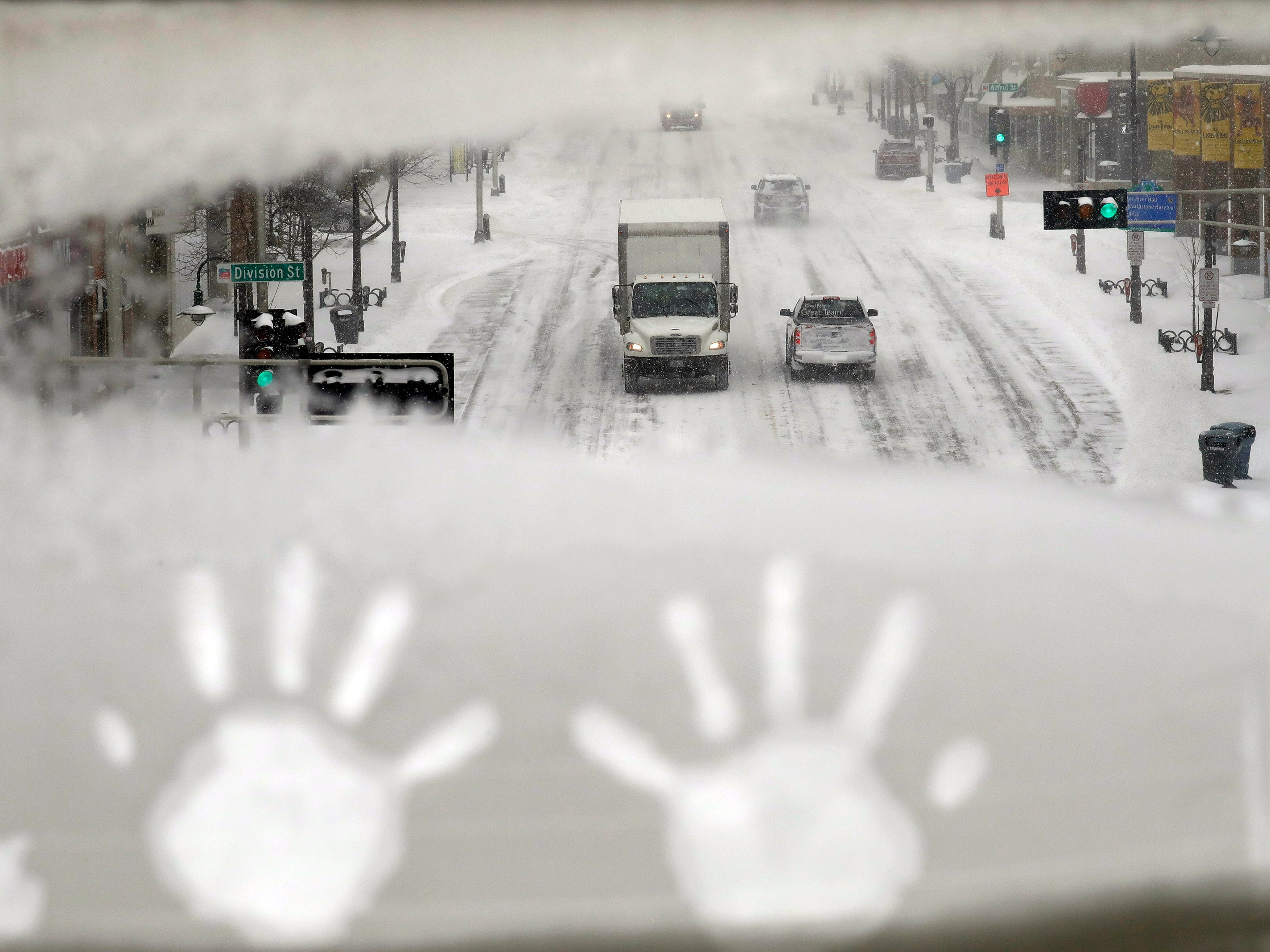 Hand prints are left behind on an overpass as traffic moves slowly along College Avenue during a snowstorm in downtown Appleton, Wis. Jan. 28, 2019.