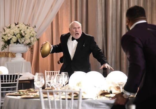 Terry Bradshaw prepares to throw a football across a ballroom.