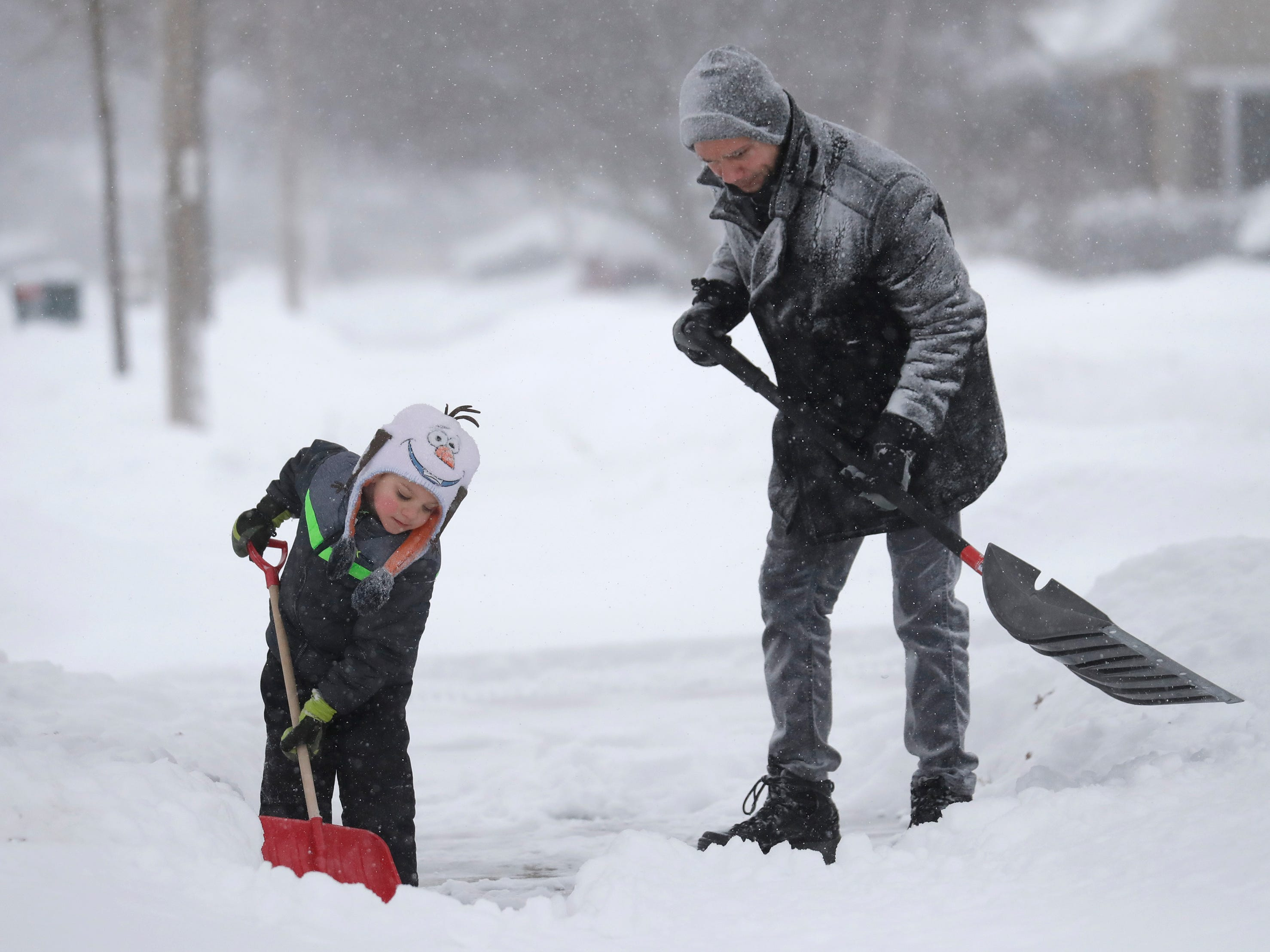 David Liebhard gets a little help from his son Levi, 4, as the two shovel their driveway during a snowstorm in Appleton, Wis., Jan. 28, 2019.