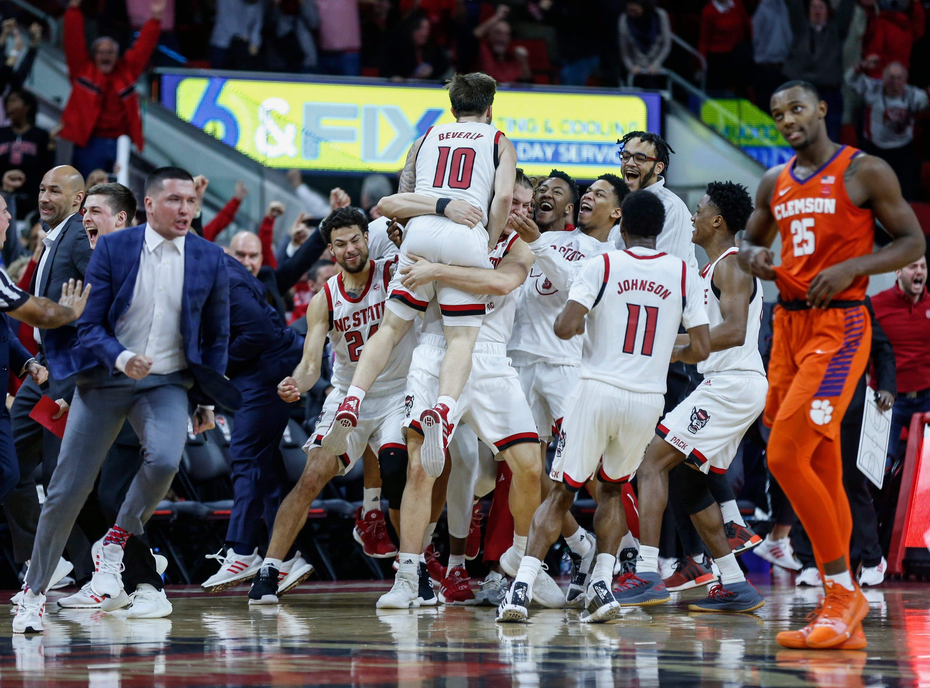 Jan 26, 2019; Raleigh, NC, USA; North Carolina State Wolfpack guard Braxton Beverly (10)  celebrates with teammates after scoring at the buzzer against the Clemson Tigers in the second half at PNC Arena. Mandatory Credit: Nell Redmond-USA TODAY Sports