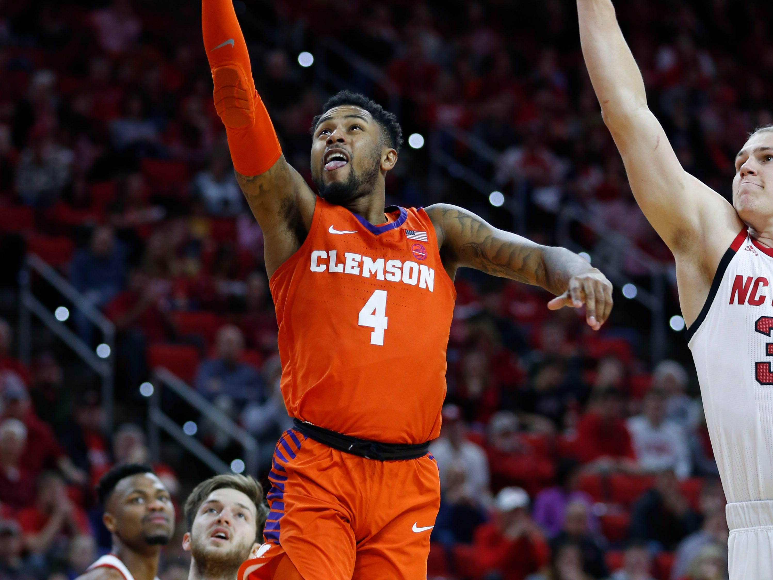 Jan 26, 2019; Raleigh, NC, USA; Clemson Tigers guard Shelton Mitchell (4) shoots the ball past North Carolina State Wolfpack guard Braxton Beverly (10) in the second half at PNC Arena. Mandatory Credit: Nell Redmond-USA TODAY Sports