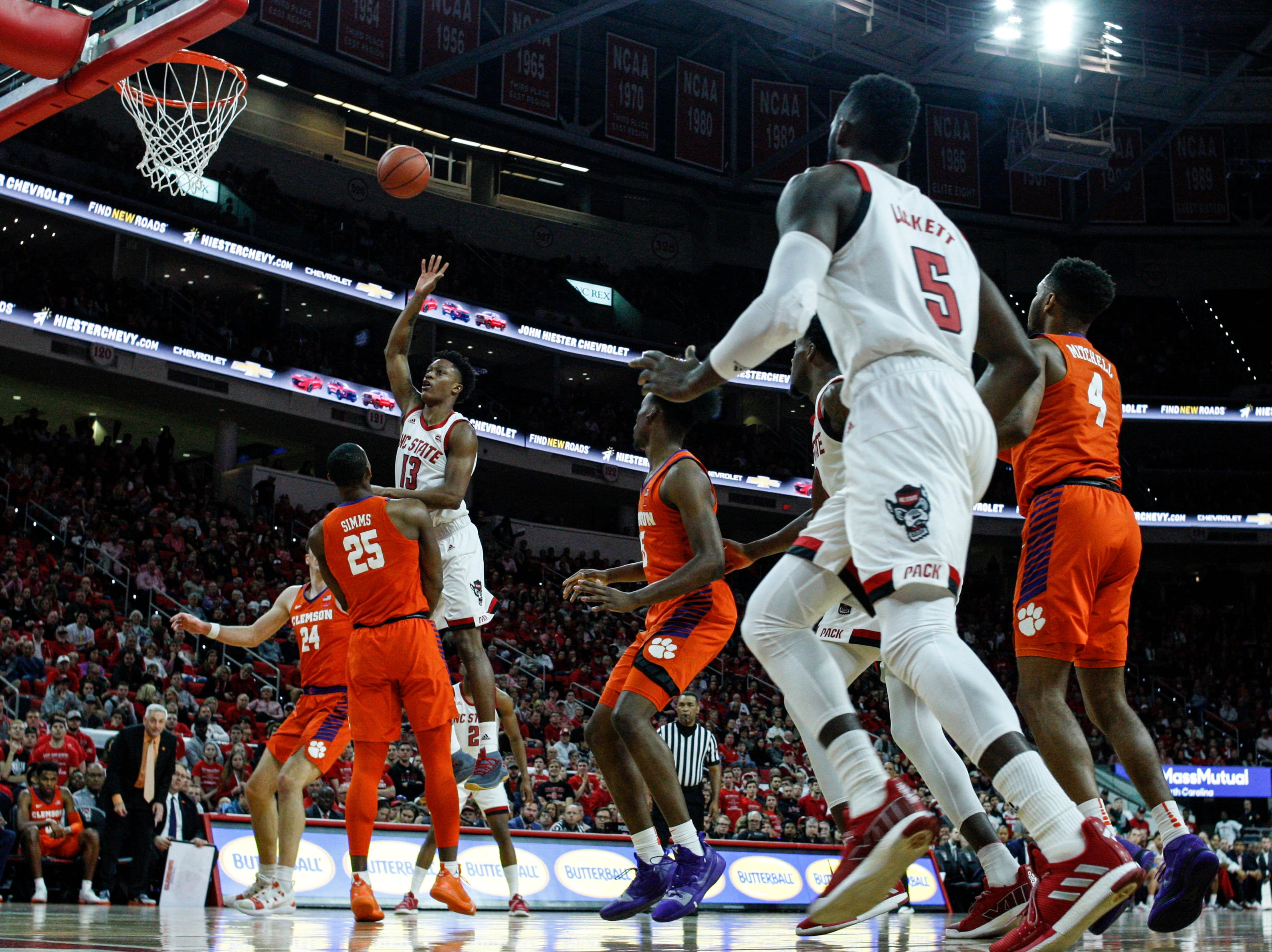 Jan 26, 2019; Raleigh, NC, USA; North Carolina State Wolfpack guard C.J. Bryce (13) shoots the ball over Clemson Tigers forward Aamir Simms (25) in the first half at PNC Arena. Mandatory Credit: Nell Redmond-USA TODAY Sports