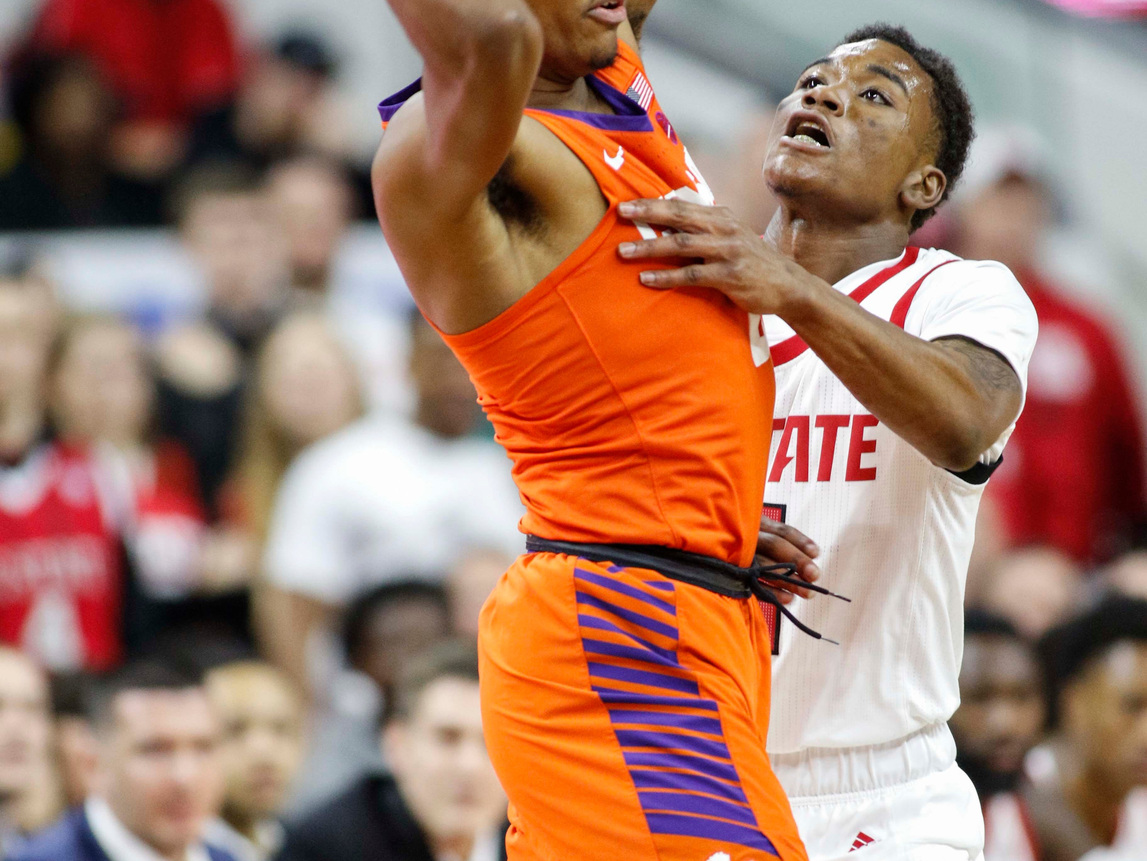 Jan 26, 2019; Raleigh, NC, USA; Clemson Tigers guard Clyde Trapp, left, keeps the ball from North Carolina State Wolfpack guard Markell Johnson (11) in the first half at PNC Arena. Mandatory Credit: Nell Redmond-USA TODAY Sports