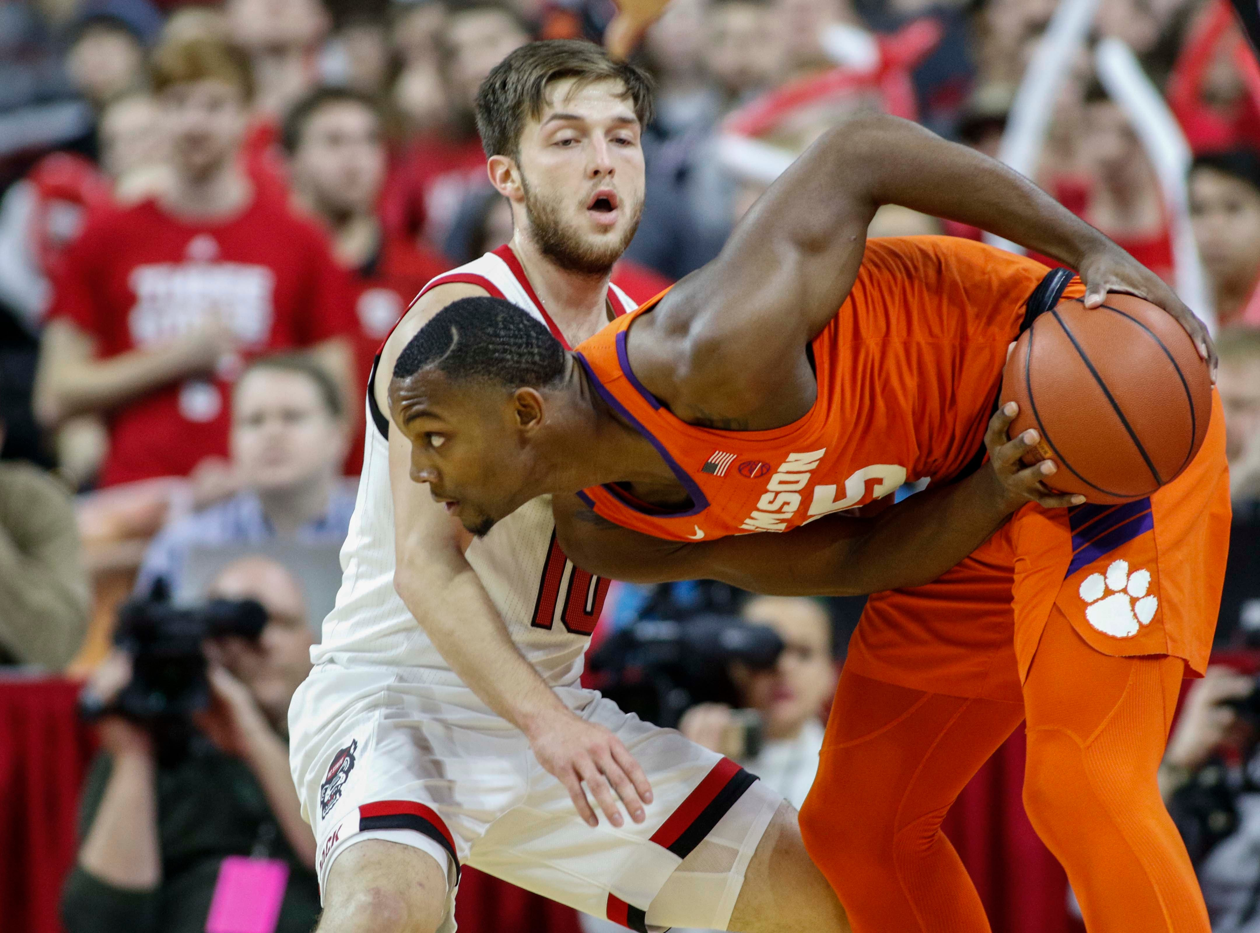 Jan 26, 2019; Raleigh, NC, USA; Clemson Tigers forward Aamir Simms (25) looks  for room to pass against North Carolina State Wolfpack guard Braxton Beverly (10) in the first half at PNC Arena. Mandatory Credit: Nell Redmond-USA TODAY Sports