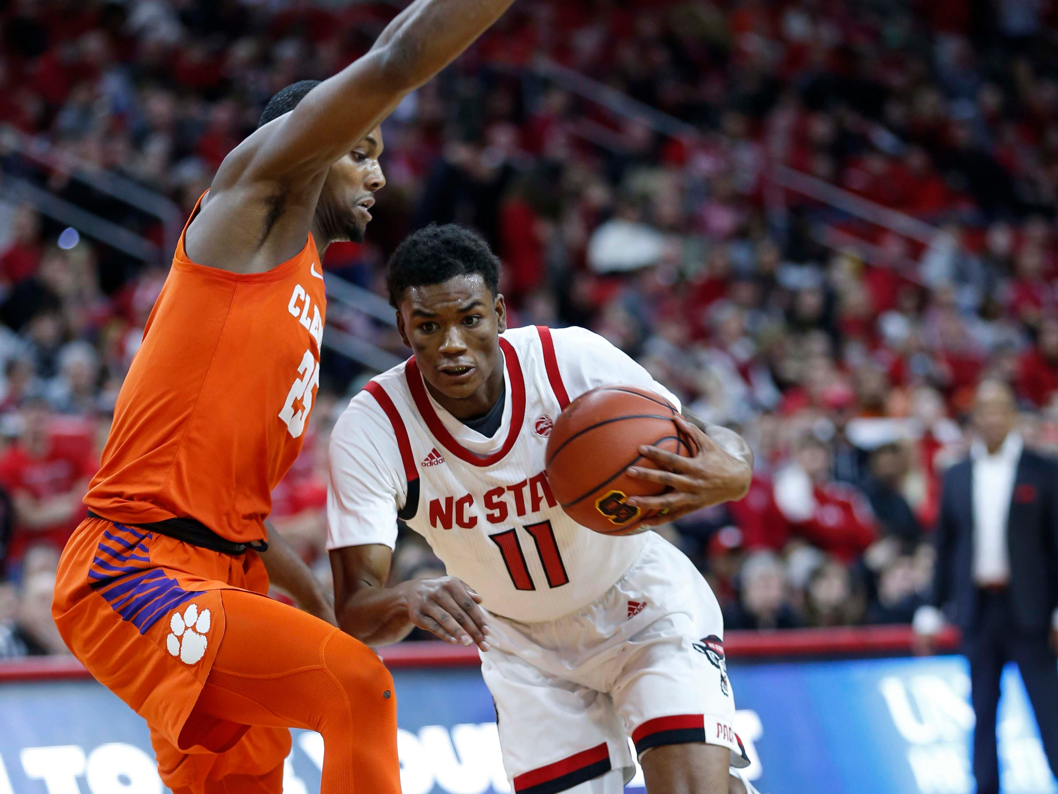 Jan 26, 2019; Raleigh, NC, USA; North Carolina State Wolfpack guard Markell Johnson (11) drives against Clemson Tigers forward Aamir Simms (25) in the first half at PNC Arena. Mandatory Credit: Nell Redmond-USA TODAY Sports