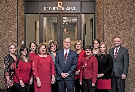 Blake Chatelain (center), president and CEO of Red River Bank, with some of the other employees who have been with the bank since its start 20 years ago.