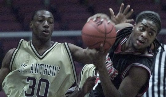 Neptune's Marquis Alston grabs a rebound in front of St. Anthony's  Obie Nwadike in the second half of the 2002 NJSIAA Tournament of Champions final at the Meadowlands.