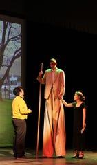 "A man on stilts (Josh Ward), accompanied by his wife (Zoe Beasley)  meets Edward Bloom (Spencer Kasselman) in this rehearsal scene in Abilene High's ""Big Fish."""