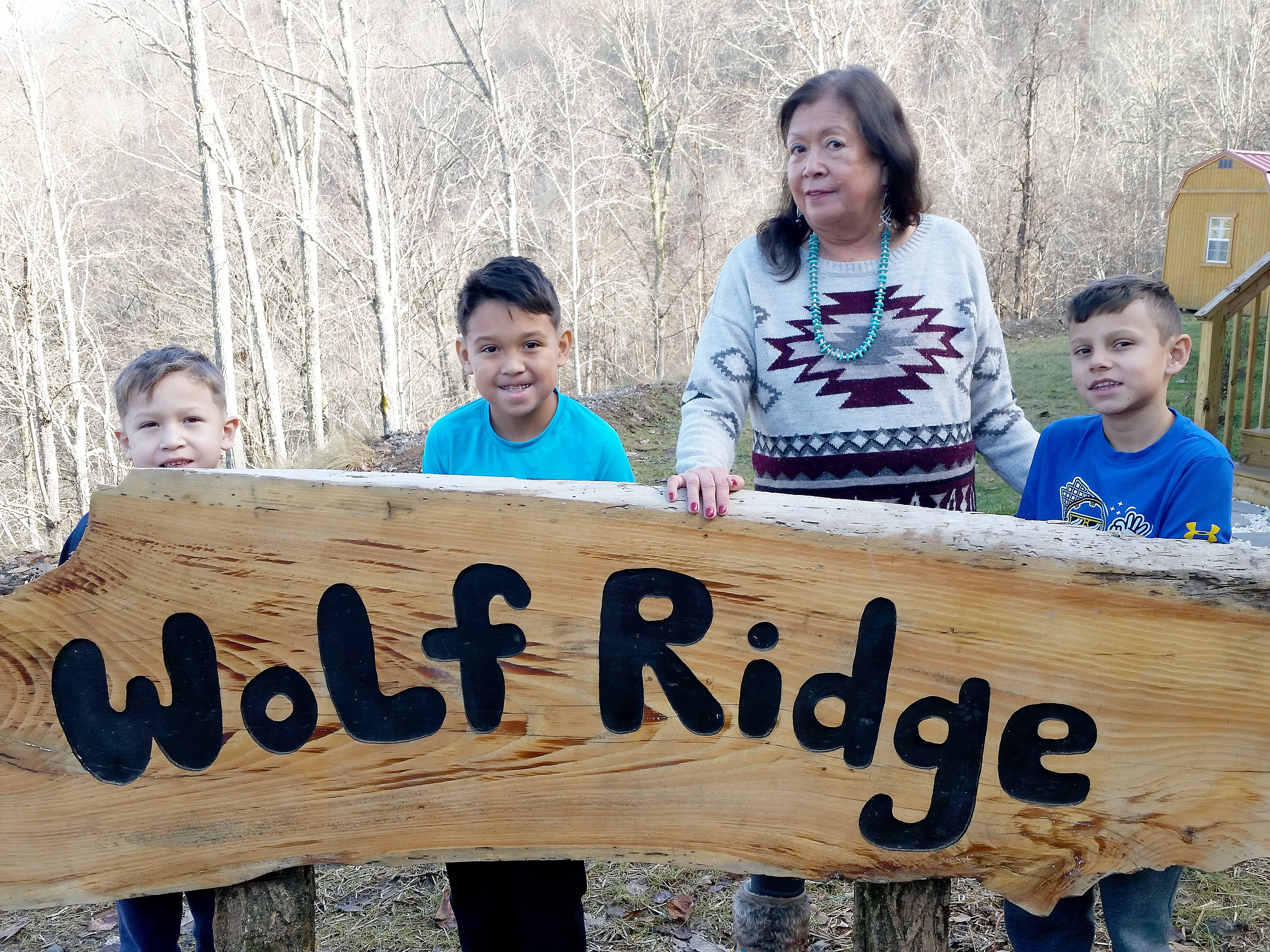 Vangie Stephens stands with her grandsons Carter, or in Cherokee Wayasdi and Kaden, or Kaniliya, Stephens and their friend Jeron Martens at her home on the Qualla Boundary.