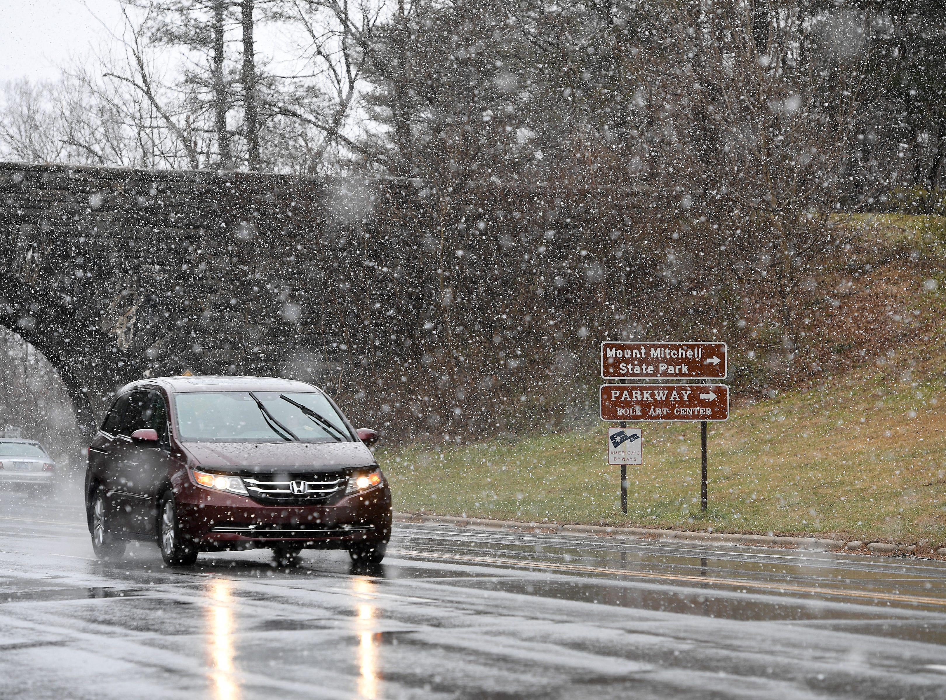 A car drives under the Blue Ridge Parkway on Tunnel Road through the snow on Jan. 29, 2019. The Parkway is closed after the open Folk Art Center and at Tunnel Road.