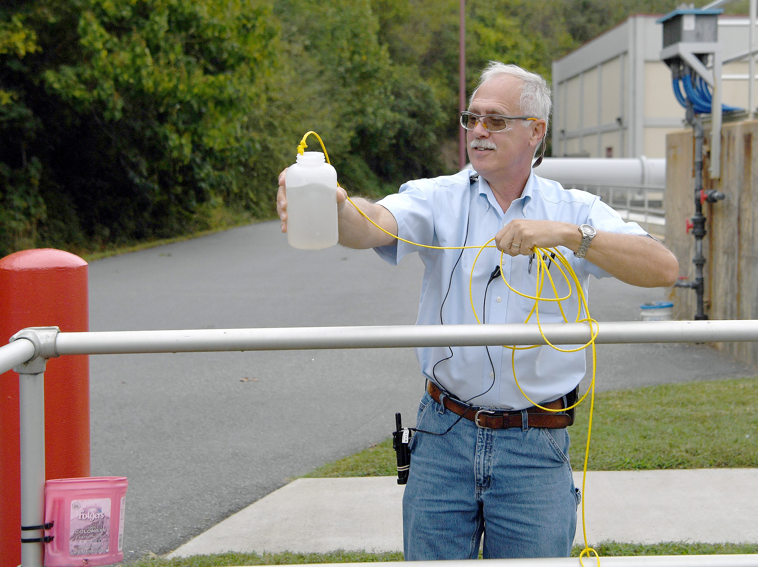 Roger Edwards, Wastewater Reclamation Facility Operations Manager, shows how clean the water leaving the facility has become after treatment as it is released back into the French Broad River as he gives a tour on Oct. 9, 2018.