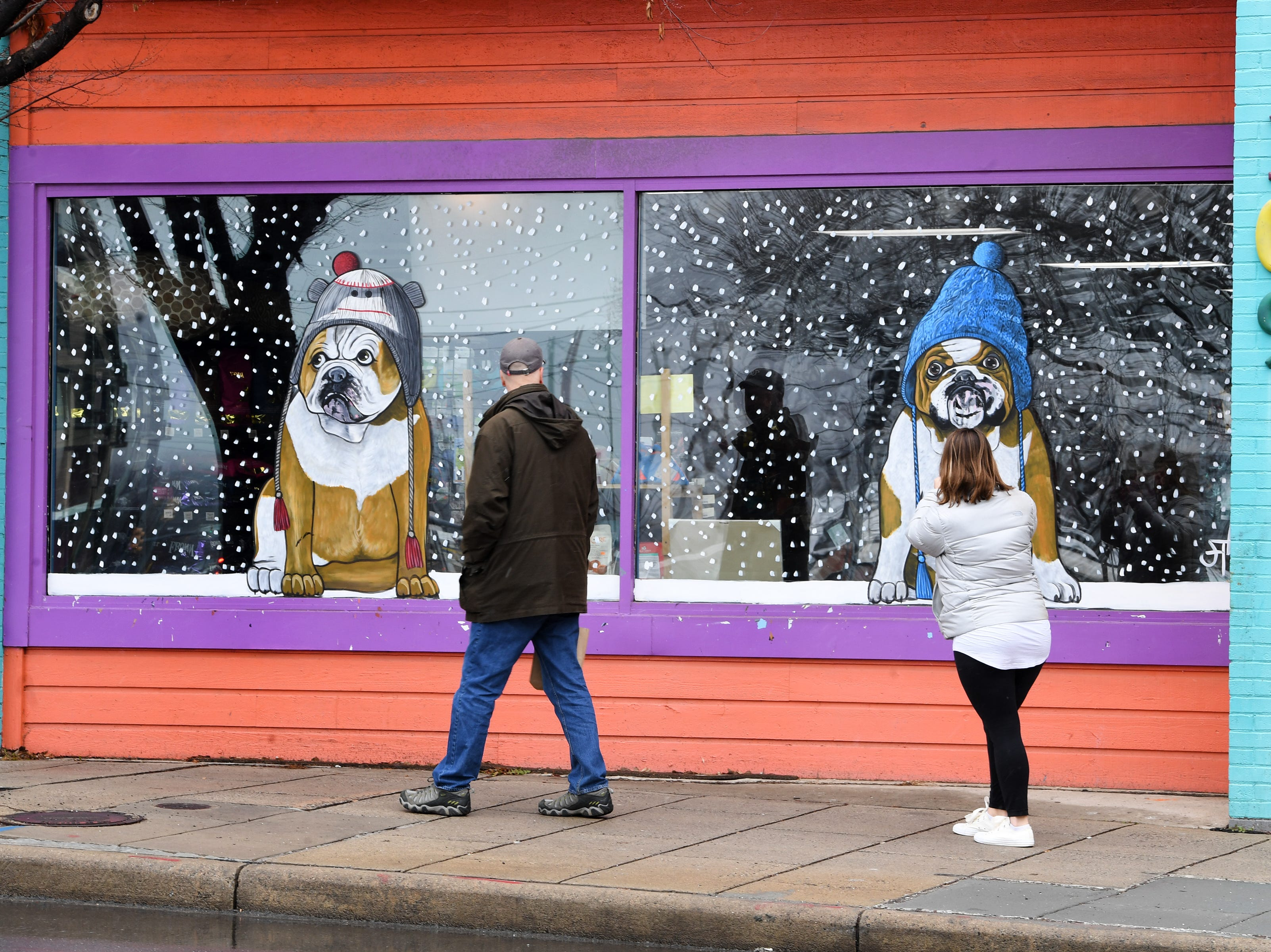 A woman stops to take a photo of a window display downtown on Jan. 29, 2019.