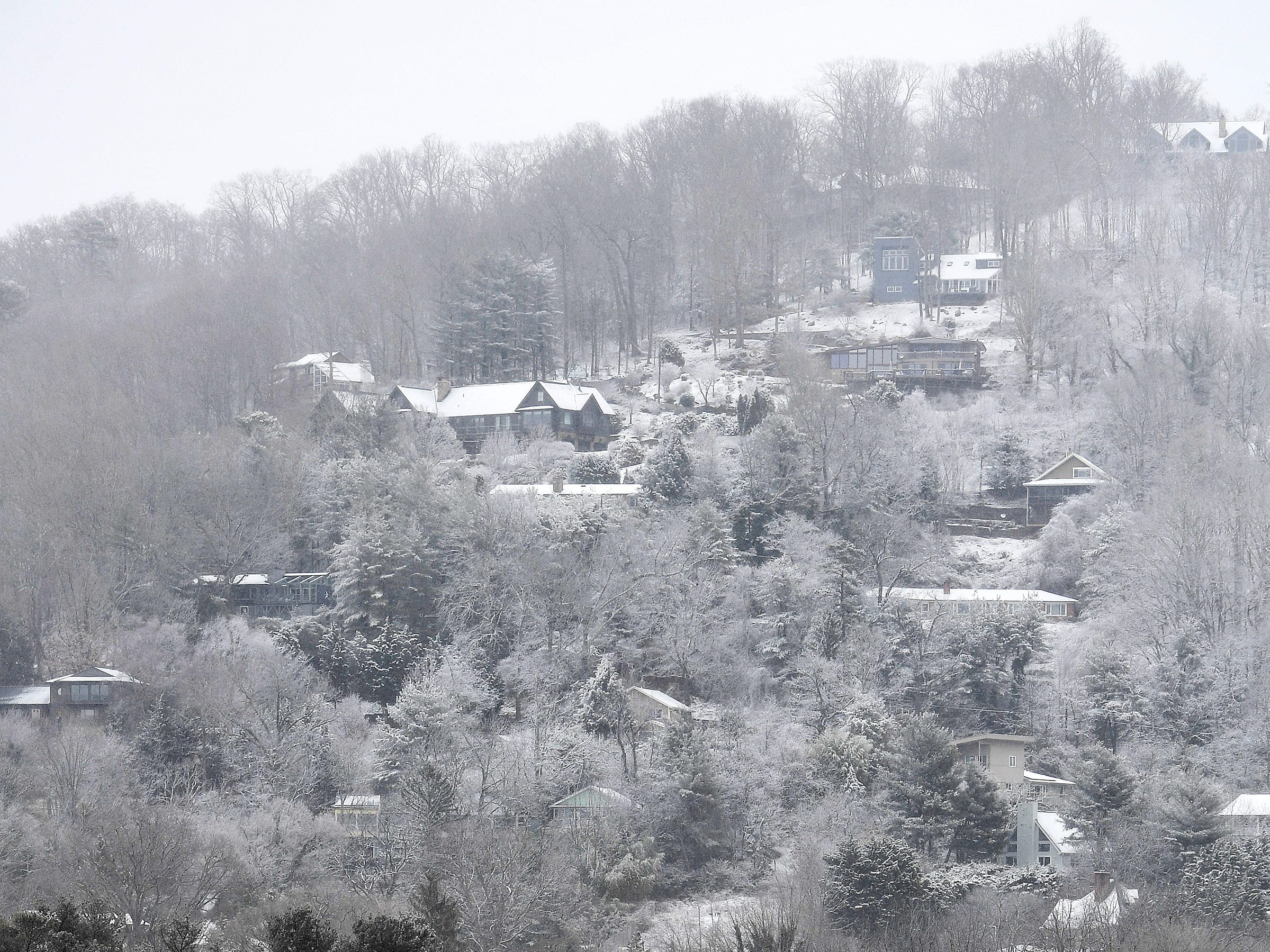 Higher elevations are blanketed in snow as downtown Asheville receives a dusting on Jan. 29, 2019. The forecast predicts up to three inches of snow and icy road conditions.