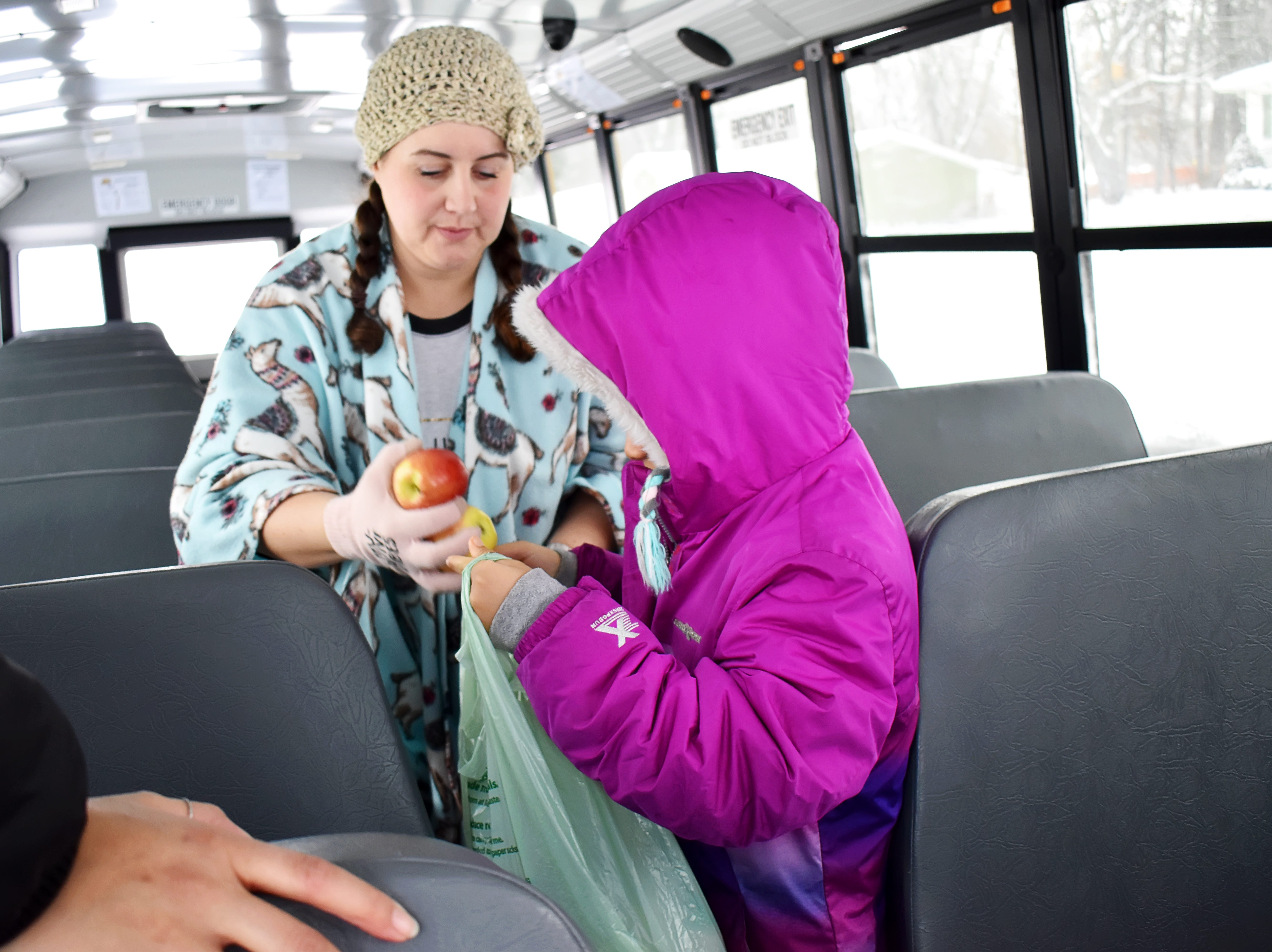 Jessica Eldridge, head of the Battle Creek Montessori Academy, helps a student fill a grocery bag with fruit and other foods the school delivered to students on Tuesday.