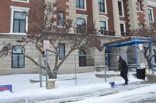 City Employee Shawn Goshorn shovels outside the city of Battle Creek offices on Tuesday. City offices closed early Tuesday and will be closed today and Thursday because of the extreme winter weather.