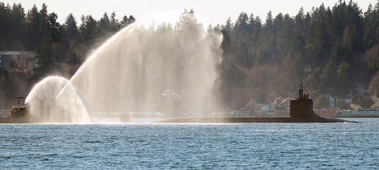 A Navy tugs sprays water as the USS Connecticut returns to Naval Base Kitsap Bremerton after a six-month deployment on Tuesday.