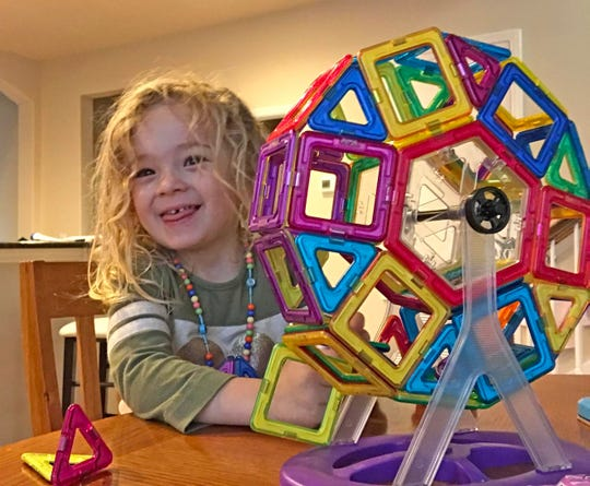 Isabella builds a ferris wheel out of her magnet set with an assist from her father.
