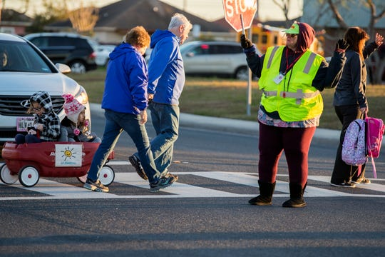 Crossing Guard Ginger Redd helps children cross the street at Mireles Elementary School on Tuesday, January 29, 2019. An arctic cold front is moving into the Coastal Bend and into the Gulf waters, according to a forecast from the National Weather Service in Corpus Christi. Lows will dip to the 40s with wind gusts as high as 39 mph.