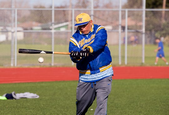 Moody High School baseball coach Joe Curiel hits balls to players during practice on Monday, January 28, 2019.