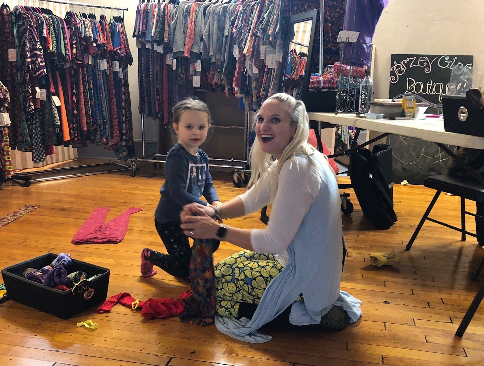 Samatha Wilbur of Jerzey Girlz Boutique, gets help from Grace Nairn, 4, at a Merchantville pop-up market. Grace's mom, Megan Grace, sets up  a table with her hand-knitted items.