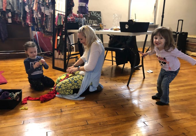 Abbie Nairn, 3, strikes a pose as her sister Grace, 4, works with Samantha Wilbur at the Merchantville pop-up market.