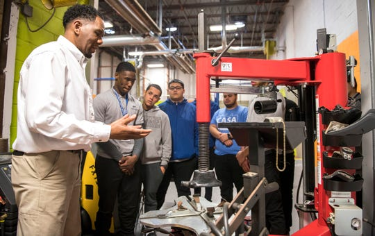 Respond, Inc. instructor Patrick Moore, left, explains how a tire machine is used to  Mastery High School students in the automotive technology training center of Respond Inc. in Camden, NJ, on Tuesday, January 29, 2019.    Respond, Inc. has partnered with Mastery High School in North Camden to train 11th and 12th graders for careers as auto technicians and mechanics.