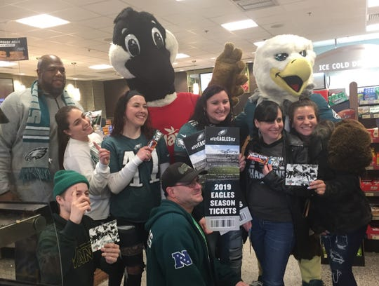 Heather Berman of Atco, holding tickets at center, poses with friends, family, mascots and former Eagle Barrett Brooks, far left, at a Cherry Hill Wawa Tuesday.