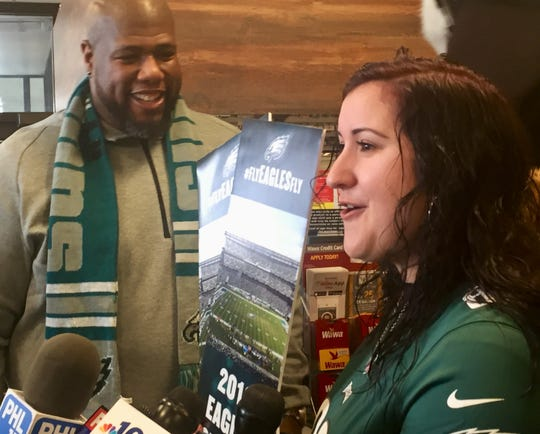 Heather Berman of Atco receives ceremonial season tickets from former Philadelphia Eagle Barrett Brooks at an event Tuesday in a Cherry Hill Wawa.