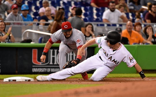 Sep 20, 2018; Miami, FL, USA; Miami Marlins catcher J.T. Realmuto (11) slides in to third base safely ahead of the tag of Cincinnati Reds third baseman Eugenio Suarez (7) in the first inning at Marlins Park. Mandatory Credit: Jasen Vinlove-USA TODAY Sports