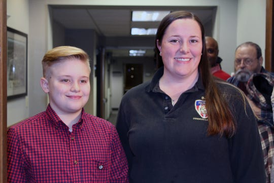 Myles Macbeth and dispatcher Amanda Robinette received plaques for their efforts after Ed Hassler needed help following a fall on the family's River Road driveway.