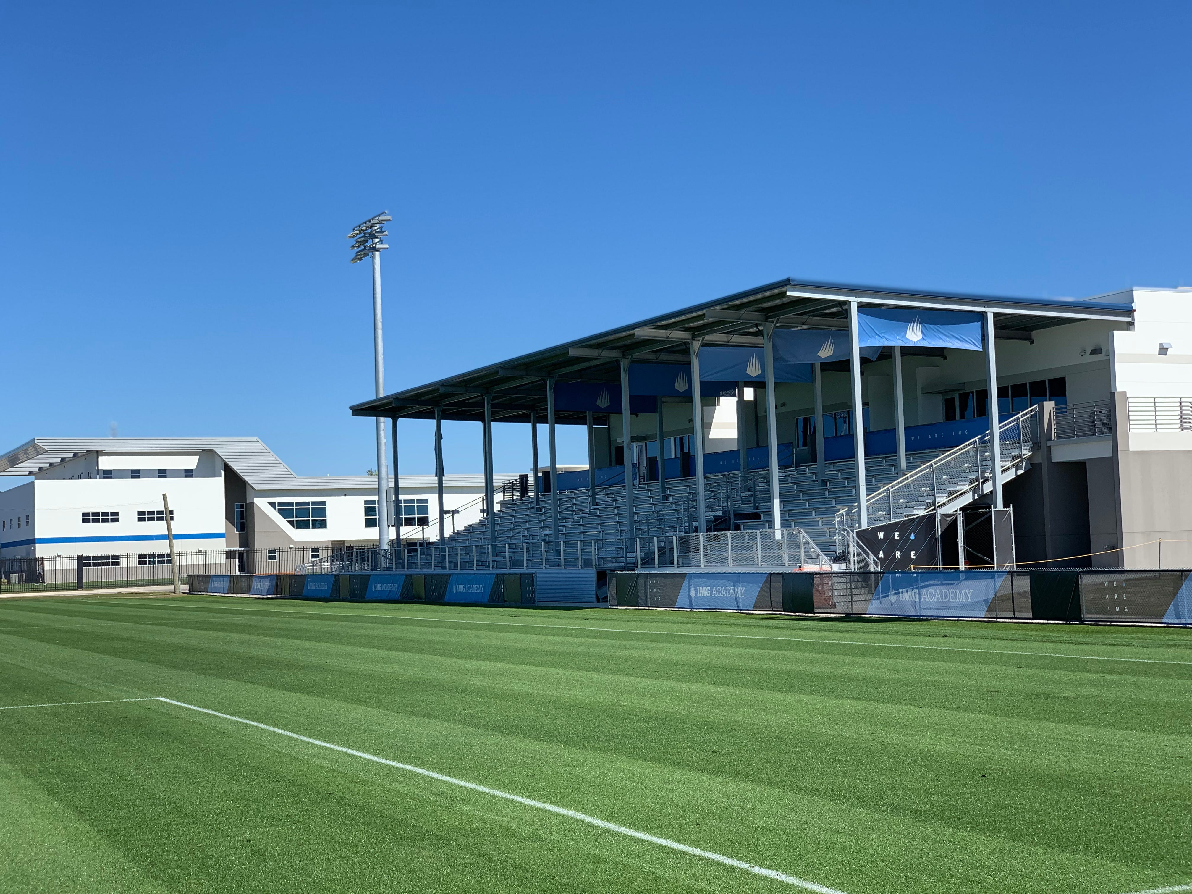IMG Academy's Soccer Complex building looks out on a match-play field, complete with grandstand for spectators.