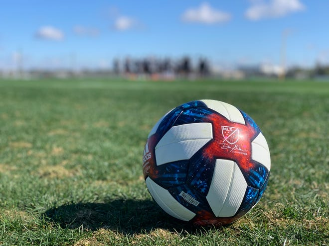 FC Cincinnati prepares for a drill in the distance. The new 2019 MLS match ball sits in the foreground.