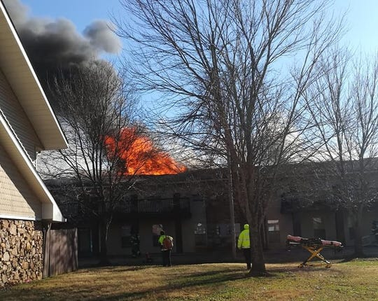 Flames pour from the roof of a building at Ashford Place Apartments on Memorial Drive on Tuesday, Jan. 29, 2019.