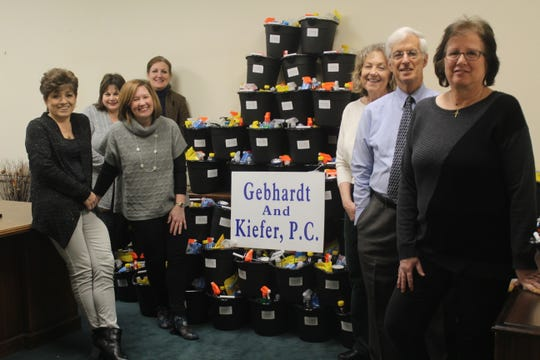 Jennifer Williford of Fisherman's Mark Food Pantry (third from left) accepts a donation of 135 buckets of household cleaning supplies from staff at Gebhardt & Kiefer Law Offices.