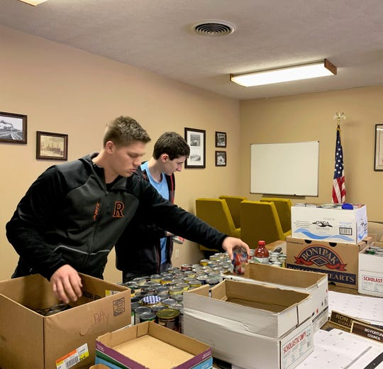 Logan Smith and Bryce Grace sort food and pack boxes for the West Lafayette Food Pantry as part of a G.I.V.E. Club community outreach project.