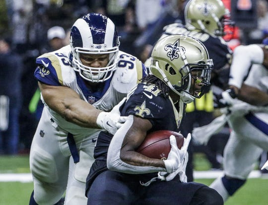 Saints RB Alvin Kamara runs from the grasp of Rams DT Ndamukong Suh in the NFC Championship game in New Orleans, Jan. 20.