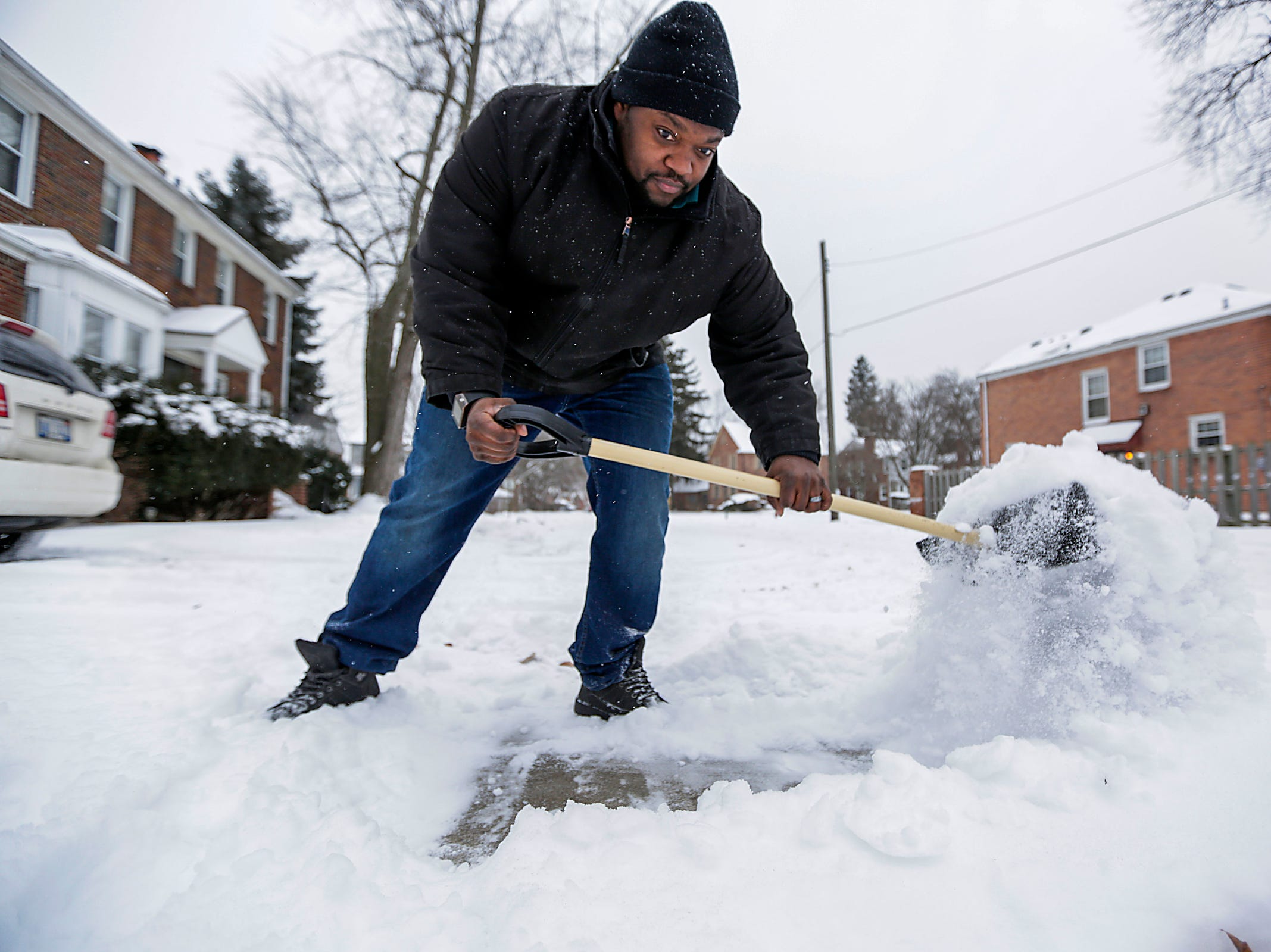On the eve of the Polar Vortex, David Collins, 36, clears the snow from the walkways and driveway in front of his home in Detroit on Tuesday, Jan. 29, 2019. Some areas of Lower Michigan could face wind chills as low as 45 degrees below zero, according to the National Weather Service.